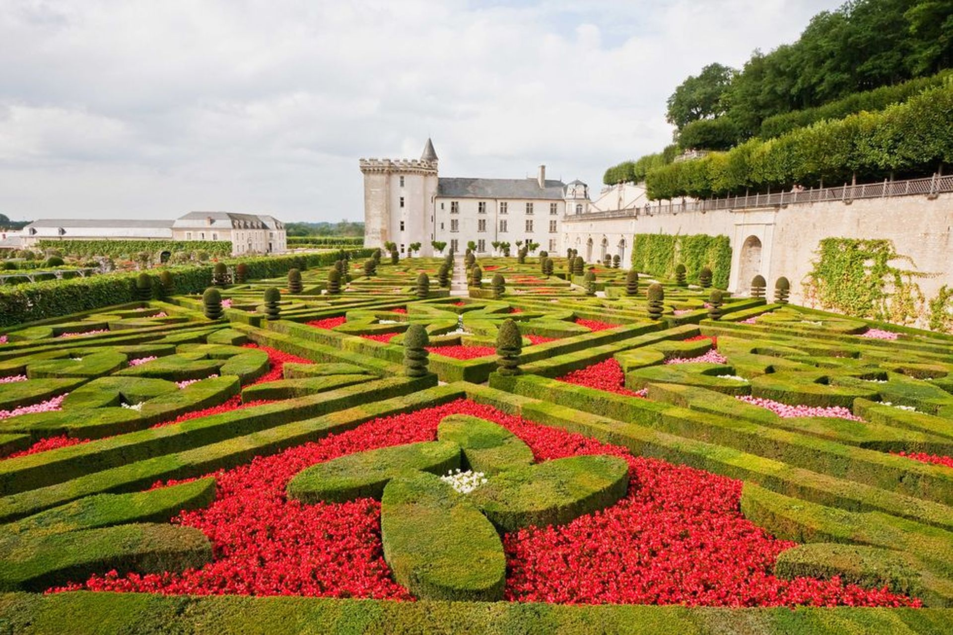beautiful gardens with figures and many roses off the paths.